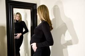 Embarazada miránose al espejo