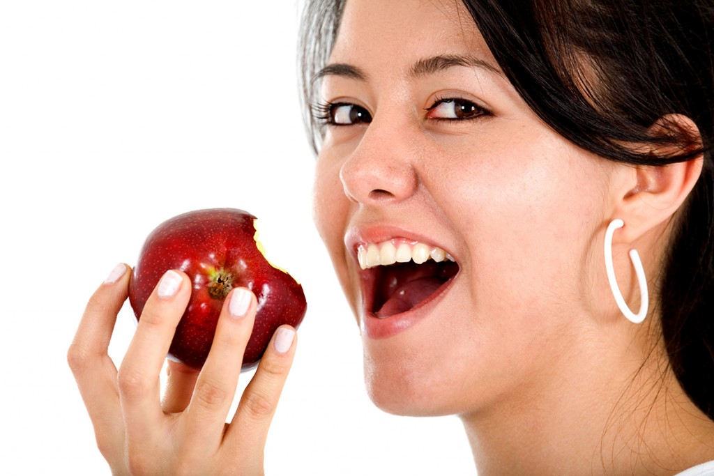 girl eating apple over white